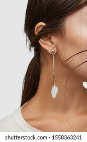 Cropped close-up shot of a brunette woman in an ivory white top and with a golden stud earring made as straight and wavy sticks with  several leaf-shaped nacre pendants.