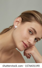 Cropped close-up shot of a charming European woman with a stud earring made as a white gem butterfly with a sparkling crystal pendant in a silver chase. The lady's blonde hair is gathered in a knot.