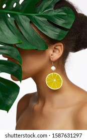 Cropped close-up shot of a dark-haired lady with an earring made as a  silver hook with a white gem block with a stylized yellow lemon-like slice. The lady's face is hidden under a tropic leaf.