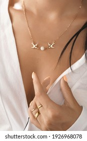 Cropped close-up shot of a lady holding her wrist near V-neckline of white blouse. The lady's neck is decorated with romantic necklace with two golden swallows and pearl bead.