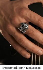 Cropped closeup shot of man's hand, touching headstock of guitar. The guy is wearing signet-ring in view of eagle. The man is wearing black clothes, posing on dark background. Trendy men's accessory.