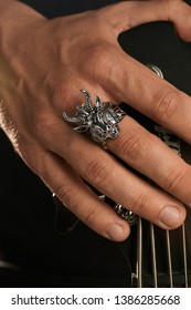 Cropped closeup shot of man's hand, touching headstock of guitar. The guy is wearing massive signet-ring in view of demon Baphomet. The man is wearing black clothes, posing against dark background.