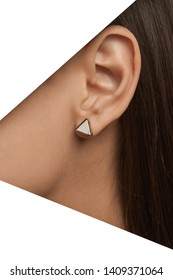 Cropped closeup side portrait of girl's head with tanned skin. The woman is wearing small stud earring with flat surface and white marbled insertion, posing behind snowy triangle-shaped foreground.