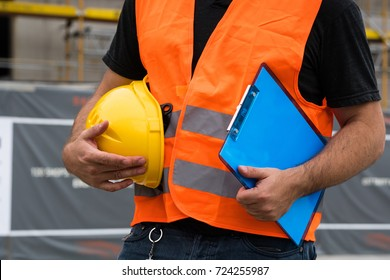 Cropped construction worker with orange safety vest holding a yellow helmet