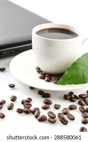 Cropped cup of black coffee with laptop, saucer, scattered coffee beans with leaf at breakfast on white background