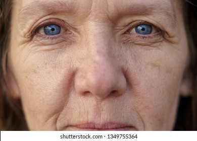 Cropped face of a blue-eyed middle-aged woman with wrinkled skin looking into the lens in a concept of ageing