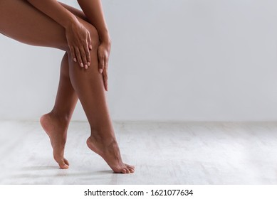 Cropped of female legs, black woman touching her skin after waxing or epilation, copy space