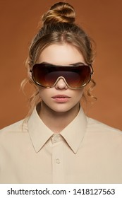 Cropped front shot of blonde lady, wearing shirt. The girl with bun and wavy hair locks in shield sunglasses with golden rim and transparent brown lenses, is looking at camera on brown background.