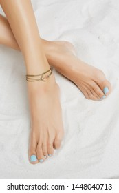Cropped front shot of lady's legs with blue pedicure, wearing ankle bracelet with double olive-colored strand, adorned with golden anchor. The girl is crossing legs, posing on the white background.