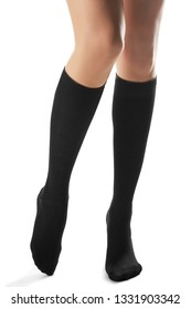 Cropped front shot of woman's slender legs wearing black knee socks. The lady is making a step against the white background. Comfortable legwear for ladies and girls. Fashionable women's hosiery.