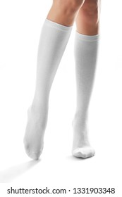 Cropped front shot of woman's slender legs wearing snowy knee high socks. The girl is making a step against the white background. Comfortable legwear for ladies and girls. Stylish women's hosiery.