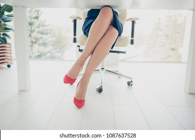 Cropped front view portrait bottom view of woman's legs wearing black skirt red high heels shoes sitting leg by foot on chair in workplace, workstation having ideal stunning perfect thin tempting legs