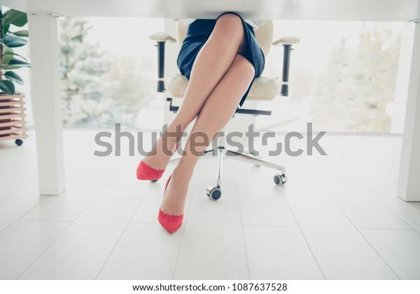 職場の椅子に黒いスカートの赤いハイヒールの靴を履いた女性の脚の下部をクロップした前面図。座る場所には、魅力的な完璧な薄い魅力的な脚を持つワークステーション