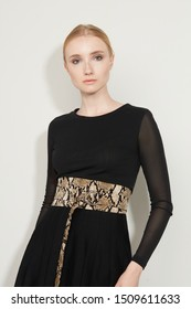 Cropped front view shot of a blond girl, wearing black dress with transparent sleeves and snake print wide belt with semicircular massive buckle. Thin part of a belt is hanging down.