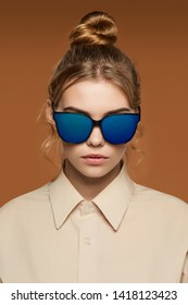 Cropped front view shot of blonde lady, wearing shirt. The girl with bun and wavy hair locks in wayfarer sunglasses with black rim and blue opalesce lenses, is looking at camera on brown background.
