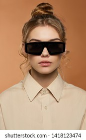 Cropped front view shot of blonde lady, wearing shirt. The girl with ballet bun and wavy hair locks in rectangle glasses with ink black rim and lenses, is looking at camera against sandy background.