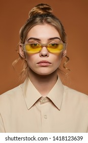 Cropped front view shot of blonde lady, wearing shirt. The girl with bun and wavy hair locks in yellow rectangle sunglasses with toreutics on the rim, is looking at camera against sandy background.