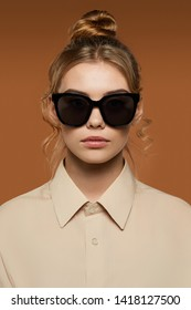 Cropped front view shot of blonde lady, wearing shirt. The girl with bun and wavy hair locks in butterfly sunglasses with ink black rim and lenses, is looking at camera against the brown background.