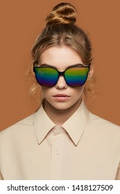 Cropped front view shot of blonde lady, wearing shirt. The girl with bun and wavy hair locks in wayfarer sunglasses with black rim and iridescent lenses, is looking at camera over brown background.