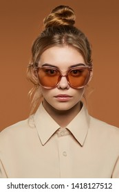 Cropped front view shot of blonde lady, wearing shirt. The girl with bun and wavy hair locks in butterfly sunglasses with light brown rim and lenses, is looking at camera against brown background.