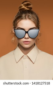 Cropped front view shot of blonde lady, wearing shirt. The girl with bun and wavy hair locks in wayfarer sunglasses with black rim and silver matte lenses, is looking at camera on brown background.