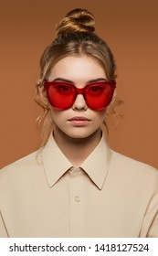 Cropped front view shot of blonde lady, wearing shirt. The girl with bun and wavy hair locks in butterfly sunglasses with rich red rim and lenses, is looking at camera against the brown background.