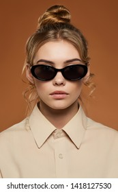 Cropped front view shot of blonde lady, wearing beige button-up shirt. The girl with bun and wavy hair locks in oval sunglasses with black rim and lenses, is looking at camera on sandy background.