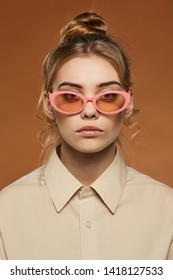Cropped front view shot of blonde lady, wearing shirt. The girl with ballet bun and wavy hair locks in oval sunglasses with pale pink rim and lenses, is looking at camera over light brown background.