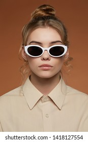 Cropped front view shot of blonde lady, wearing shirt. The girl with ballet bun and wavy hair locks in oval sunglasses with snowy and black lenses, is looking at camera over light brown background.
