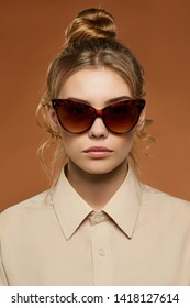 Cropped front view shot of blonde lady, wearing shirt. The girl with bun and wavy hair locks in butterfly sunglasses with brown rim with flame pattern, is looking at camera on the brown background.