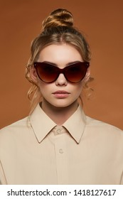Cropped front view shot of blonde lady, wearing shirt. The girl with bun and wavy hair locks in butterfly-shaped sunglasses with brown rim and lenses, is looking at camera against brown background.