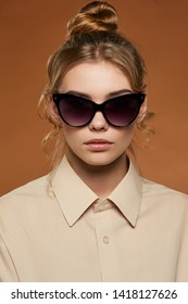 Cropped front view shot of blonde lady, wearing shirt. The girl with bun and wavy hair locks in butterfly-shaped sunglasses with black rim and lenses, is looking at camera against brown background.