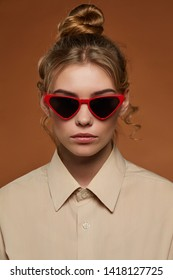 Cropped front view shot of blonde lady, wearing shirt. The girl with bun and wavy hair locks in cat eye-shaped sunglasses with rich red rim and black lenses, is looking at camera on brown background.