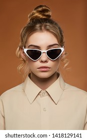 Cropped front view shot of blonde lady, wearing shirt. The girl with bun and wavy hair locks in cat eye-shaped sunglasses with white rim and black lenses, is looking at camera on brown background.