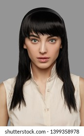 Cropped front view shot of girl with ink black straight hair with fringe, wearing sleeveless shirt with standup collar. The lady with black flicks is looking at camera, posing on gray background.