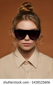 Cropped front view shot of lady, wearing shirt. The girl with ballet bun and wavy hair locks in wrap-shaped sunglasses with black rim and lenses. The woman is looking at camera over brown background.