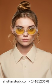 Cropped front view shot of lady with fair hair, wearing shirt. The girl with bun and wavy hair locks in oval-shaped glasses with glitter in yellow lenses, is looking at camera over brown background.