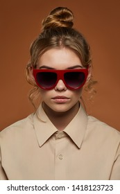 Cropped front view shot of lady, wearing shirt. The girl with bun and wavy hair locks in wrap sunglasses with rich red rim and wine red lenses. The woman is looking at camera over brown background.