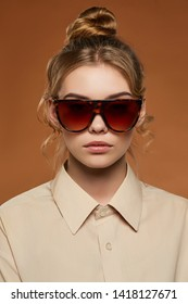 Cropped front view shot of lady, wearing shirt. The girl with bun and wavy hair locks in wrap sunglasses with brown leopard pattern rim and lenses. The woman is looking at camera on brown background.