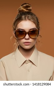 Cropped front view shot of lady with fair hair, wearing shirt. The girl with bun and wavy hair locks in oval-shaped sunglasses with leopard pattern rim, is looking at camera on the brown background.