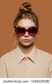 Cropped front view shot of lady with fair hair, wearing beige shirt. The girl with bun and wavy hair locks in oval-shaped sunglasses with red rim, is looking at camera on the light brown background.