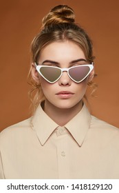 Cropped front view shot of lady, wearing shirt. The girl with bun and wavy hair locks in cat eye-shaped sunglasses with white rim and chameleon lenses, is looking at the camera on brown background.