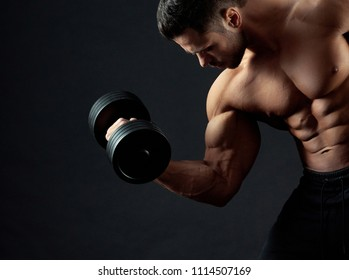 Cropped frontview of strong bodybuilder with clear muscular relief lifting heavy dumbbell in gym. Sport lifestyle. Regular gym trainings. Fit sporty body. Lifestyle. Looking healthy and sexy.