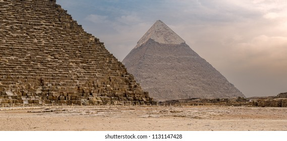 Cropped Great pyramid of Khufu and Pyramid of Khafre in the far distance with cloudy sky background located at Giza government, Cairo, Egypt