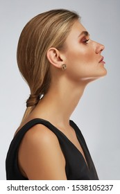 Cropped half-turn shot of a blond girl, posing on a grey background. She is wearing black tank top and golden mother-of-pearl heart earrings. Her hair pulled back in a ponytail.