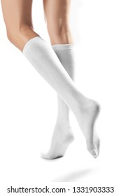 Cropped half-turn shot of girl's slender legs wearing snowy knee high socks. The woman is making a step against the white background. Comfortable legwear for ladies and girls. Trendy women's hosiery.