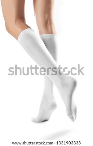 5c035f1eef8 Cropped half-turn shot of girl s slender legs wearing snowy knee high socks.  The