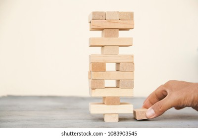 Cropped hand arrange the wooden block on table with white background.