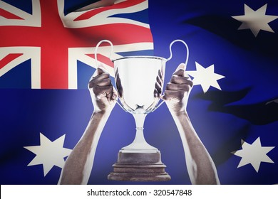 Cropped hand of athlete holding trophy against close-up of australian flag