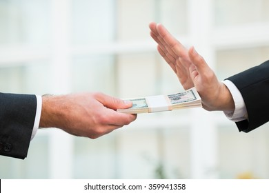 Cropped hand of businessman refusing to take bribe from partner outdoors